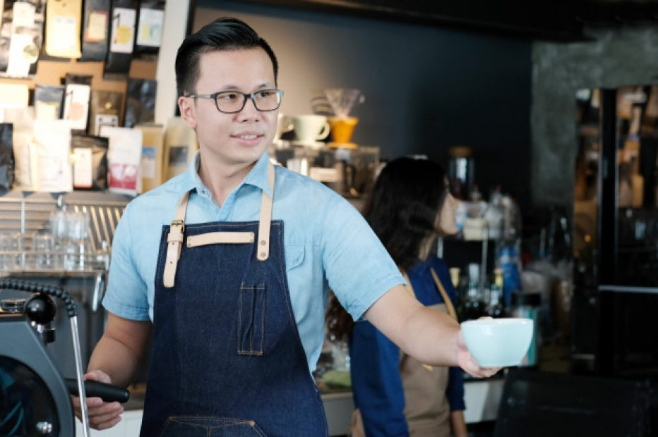 young-asian-man-barista-serving-coffee-cup-with-smiling-face-cafe-counter-background_7190-1346